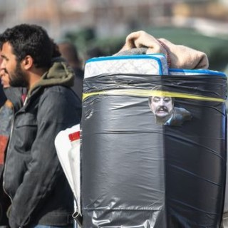 "A photo of Italian interior minister Matteo Salvini is sticked on remains of belongings of a makeshift migrants' camp known as ""The Baobab"" during the camp's eviction by police forces in Rome on November 13, 2018. - Police started to evict early on November 13 with bulldozers the camp that had been hosting hundreds of migrants, as well as Italian citizens, as buses brought the migrants to immigration offices. Interior minister Matteo Salvini commented he was determined to put an end to ""illegal free zones"". (Photo by Tiziana FABI / AFP)"